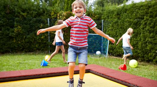 Little boy jumping on the kindergarten trampoline Wehrfritz FUN XL Kindergarden