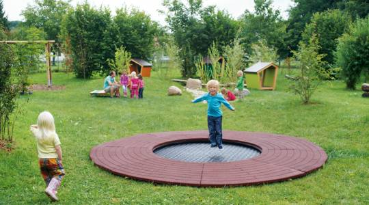 Little boy jumping on the round playground trampoline Wehrfritz Ground Trampoline round