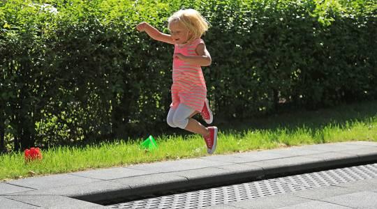 Spielplatz-Trampolin Kids Tramp Track auf einem Spielplatz mit springendem Mädchen