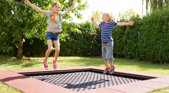 Picture of two little girls jumping on the playground trampoline Wehrfritz FUN XL against vandalism