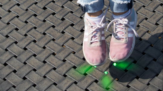 Feet of a girl jumping on a Eurotramp playground trampoline with green LED lights.