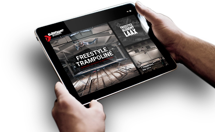 Picture of two hands holding an iPad showing the new Eurotramp Freestyle website.